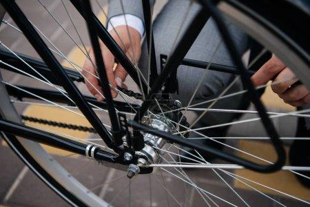 cropped view of businessman repairing bicycle wheel