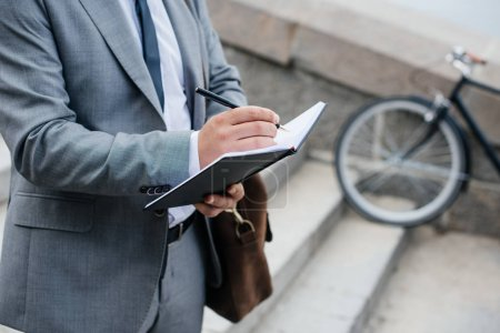 cropped view of businessman with leather bag writing in diary