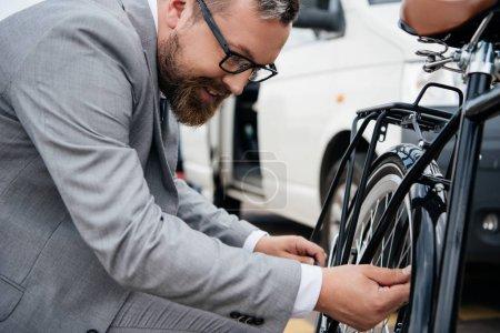 bearded businessman in suit repairing bicycle wheel