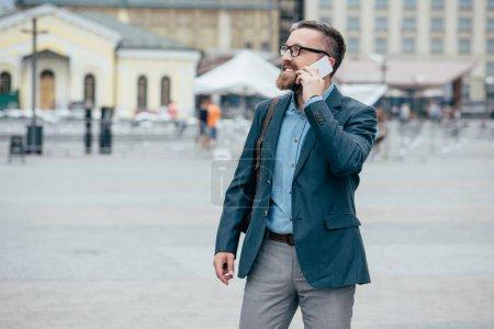 Photo pour Homme d'affaires élégant barbe parler sur smartphone en ville - image libre de droit