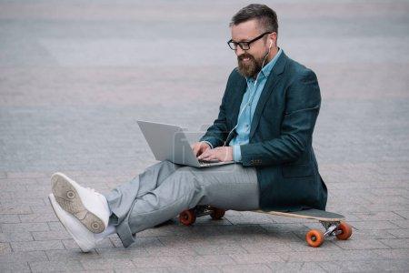 Photo pour Élégant homme européen à l'aide d'ordinateur portable et assis sur une planche à roulettes dans la ville - image libre de droit
