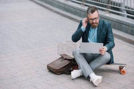 bearded man using laptop with earphones and sitting on skateboard in city