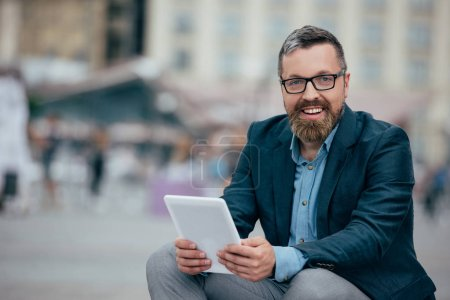 Photo for Beard stylish businessman in glasses using digital tablet in city - Royalty Free Image