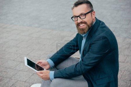 Photo pour Homme d'affaires souriant barbe en costume et lunettes à l'aide d'une tablette numérique - image libre de droit
