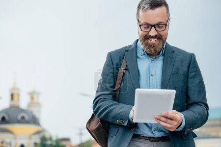Photo for Beard businessman in eyeglasses using digital tablet in city - Royalty Free Image