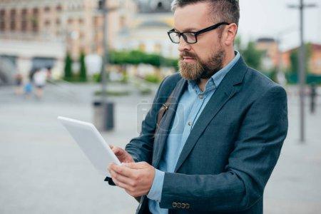 Photo pour Homme d'affaires de barbe beau dans des verres à l'aide de tablette numérique dans la ville - image libre de droit