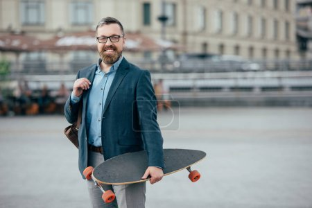 Photo for Stylish bearded man with leather bag and skateboard in city - Royalty Free Image