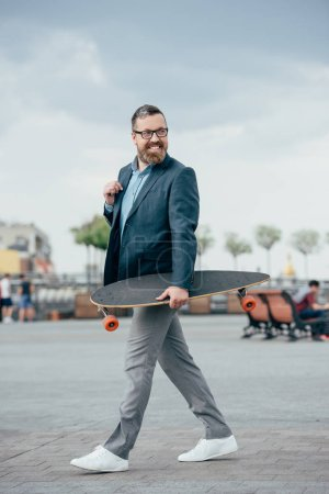 Photo for Handsome bearded man with longboard walking in city - Royalty Free Image