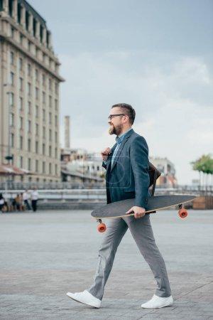 Photo pour Élégant beau barbu homme avec promenade dans la ville de skateboard - image libre de droit