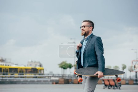 Photo for Stylish bearded man with skate walking in city - Royalty Free Image