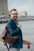 """Постер, картина, фотообои """"стильный мужчина с кожаный рюкзак и longboard в городе"""""""