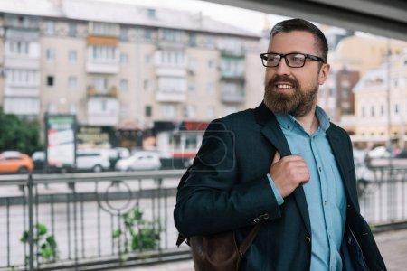 Photo pour Barbe homme élégant en lunettes avec sac en cuir en ville - image libre de droit