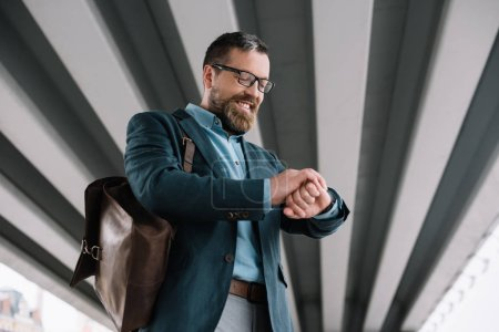 bottom view of beard stylish businessman with leather bag looking at wristwatch