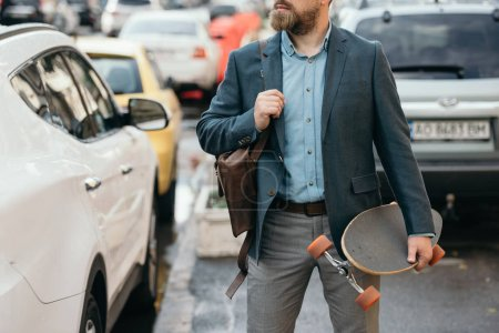 cropped view of man with leather bag and longboard walking in city with cars