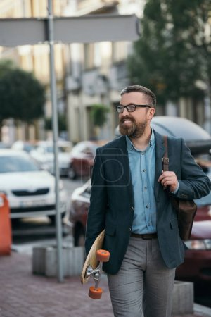 handsome bearded man with leather backpack and skateboard walking in city