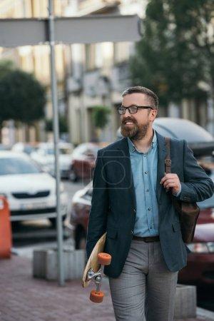 Photo pour Beau barbu homme avec sac à dos en cuir et promenade dans la ville de skateboard - image libre de droit