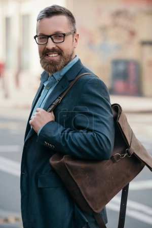 Photo for Portrait of stylish cheerful bearded man with leather bag walking in city - Royalty Free Image