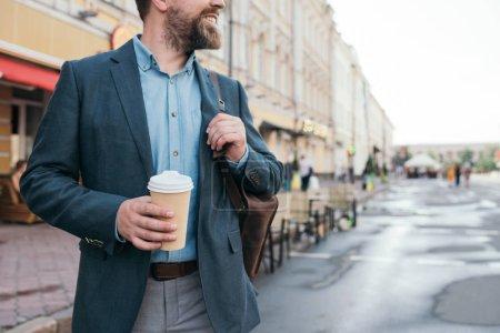 Photo pour Recadrée de l'homme avec le café pour se promener dans la ville - image libre de droit