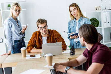 multicultural colleagues working on startup project in office and looking at coworker
