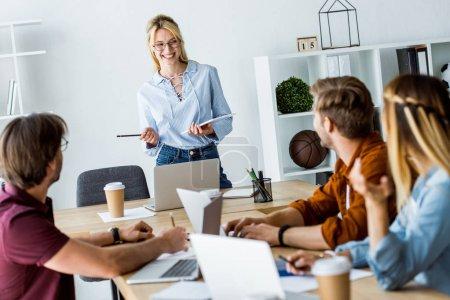 Photo pour Collègues travaillant sur le projet de démarrage dans le bureau et l'écoute de gestionnaire avec présentation - image libre de droit