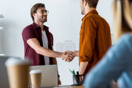 colleagues working on startup project in office and men shaking hands