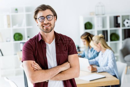handsome man standing with crossed arms in office of startup project and looking at camera