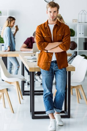 serious handsome man leaning on table in start up office