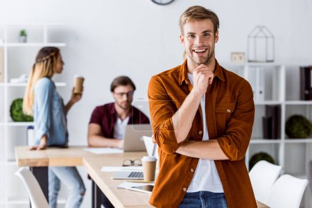 smiling handsome man leaning on table in start up office
