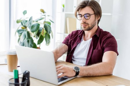handsome young businessman working on startup project in office with laptop