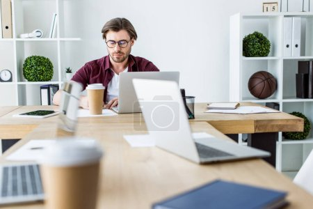 handsome businessman working on startup project in office with laptops on table