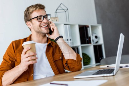 smiling handsome businessman working on startup project in office and talking by smartphone