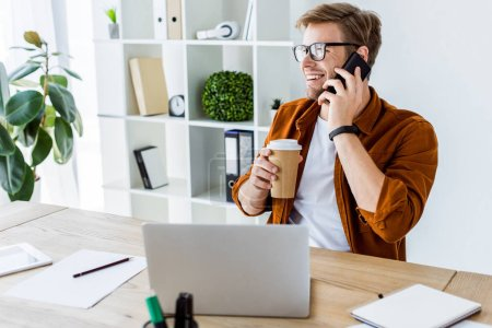 handsome businessman working on startup project in office and talking by smartphone