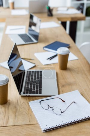 laptops with disposable coffee cups on table in business office