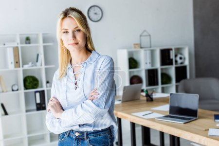 beautiful businesswoman standing with crossed arms in office