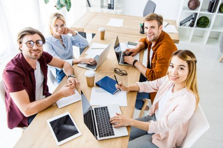 Photo for High angle view of multicultural colleagues working on startup project in office with gadgets and looking at camera - Royalty Free Image