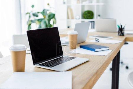 Photo pour Ordinateur portable avec écran vierge et tasses à café jetables sur la table dans le bureau d'affaires - image libre de droit