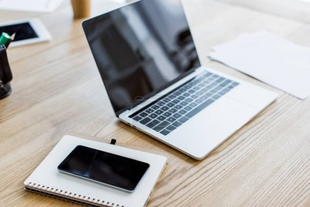 Photo pour Portable, smartphone et ordinateur portable sur la table au bureau d'affaires - image libre de droit