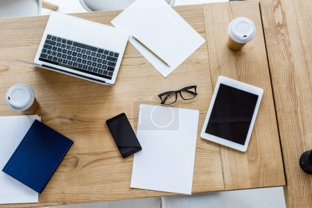 elevated view of laptop, smartphone and tablet on table in business office