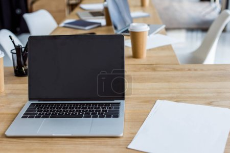 Photo for Laptop with blank screen on wooden table in business office - Royalty Free Image