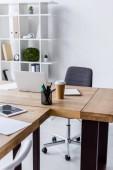 ordinateur portable et tasse à café jetable sur table au bureau d'affaires
