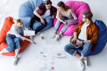 high angle view of multicultural colleagues discussing startup project in office