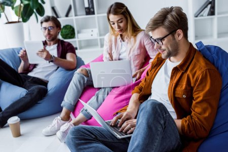 Photo for Multicultural colleagues working on startup project in office and sitting on bean bag chairs - Royalty Free Image