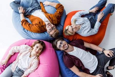 top view multicultural colleagues of startup project lying on bean bag chairs in office