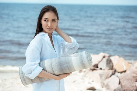 attractive asian woman holding yoga mat and looking away by sea