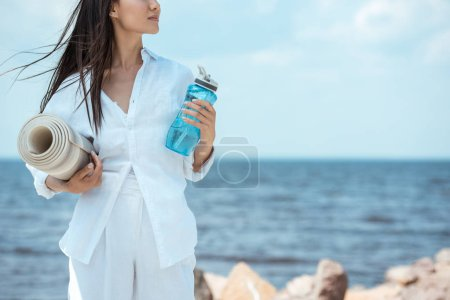 cropped image of young woman holding sport bottle of water and yoga mat by sea