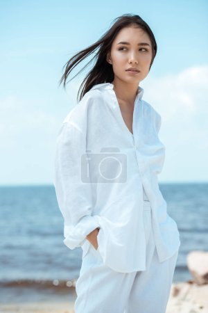 Photo for Attractive young asian woman with hands in pockets looking away on beach - Royalty Free Image