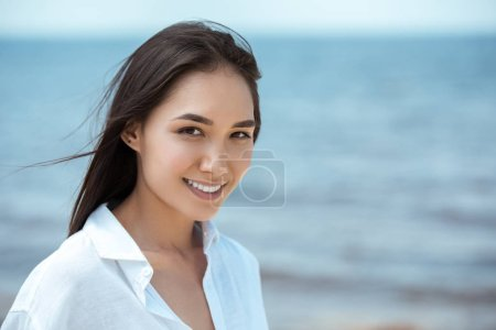 close up portrait of attractive smiling asian woman by sea