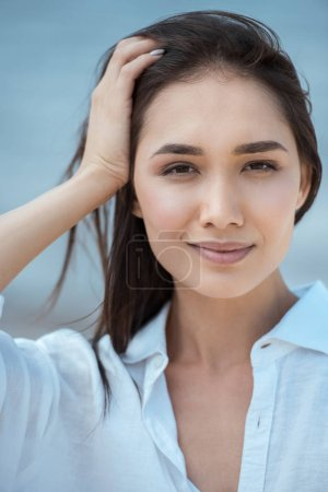 close up portrait of attractive asian woman with hand in hair on blurred background