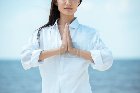 partial view of asian woman doing namaste mudra gesture in front of sea