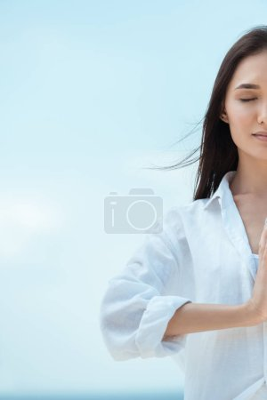 partial view of asian woman with closed eyes doing namaste mudra (salutation seal) gesture against blue sky